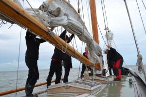 Práce na palubě s hlavní plachtou.
