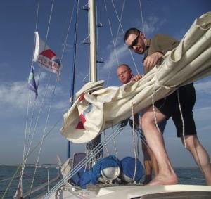 Kapitán s plavčíkem skládají hlavní plachtu.