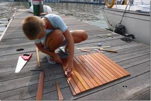 Janička připravuje prkénka z obložení, kterými jsme zároveň pobili i odklápěcí víko sedačky.